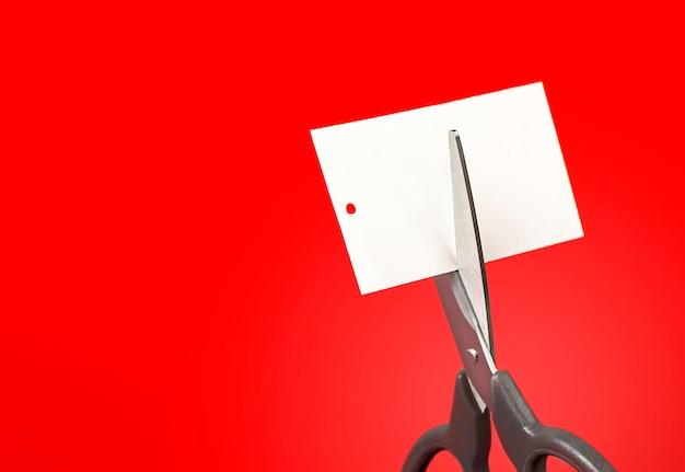 Schaar die een label op een rode achtergrond snijdt close-up