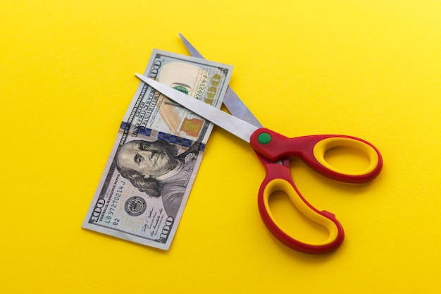 Schaar en 100 dollar biljet op gele achtergrond.