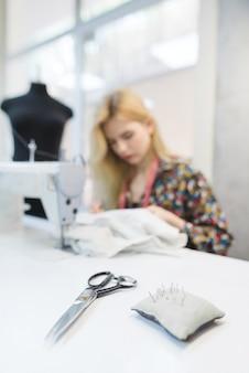 Schaar en kussen met naalden op de achtergrond van naaisters werken op de werkplek
