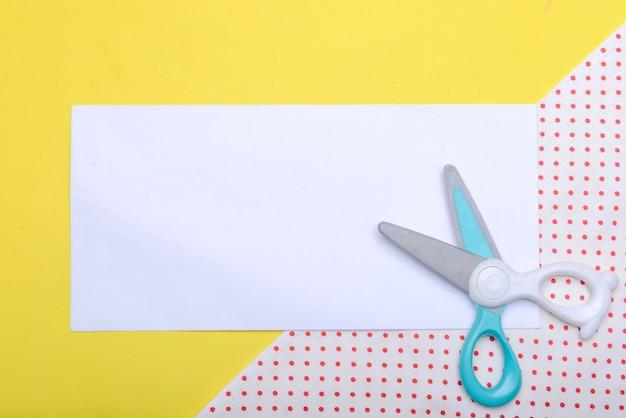Schaar en leeg wit papier met een gekleurde achtergrond. leeg witboek voor exemplaarruimte