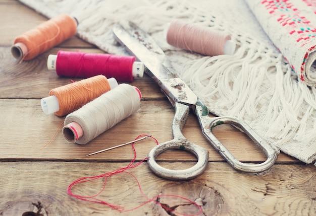 Schaar, klossen met draad en naalden, gestreepte stof. oude naaiende hulpmiddelen op oude houten