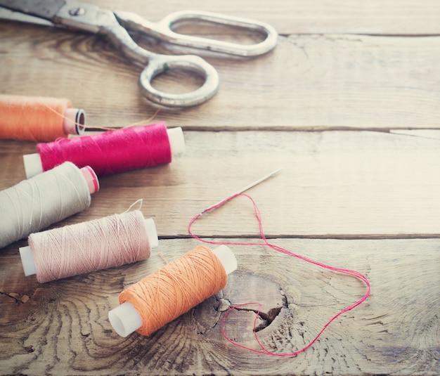 Schaar, klossen met draad en naalden. oude naaiende hulpmiddelen op oude houten