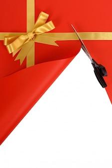 Schaar snijden open rode en gouden kerstcadeau