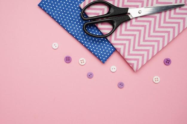 Schaar, stoffen en knoppen voor het naaien met kopie ruimte