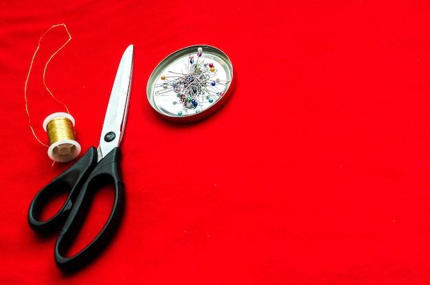 Schaar voor snijden, naalden en draad op een rode doek. conceptontwerp kleding.