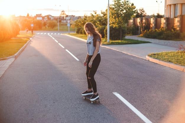 Schaatsermeisje die op straat tegen zonsondergang berijden. buitenshuis.