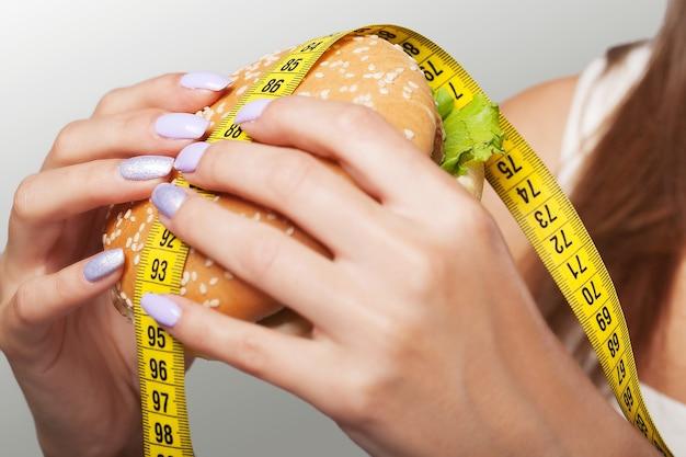Schadelijk voedsel. de keuze tussen kwaadaardig eten en sport. mooi jong meisje op een dieet. het concept van schoonheid en gezondheid. op een grijze achtergrond.