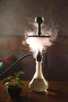 Schadelijke gewoonte om een waterpijp in een bar te roken voor ontspanningsconcept.