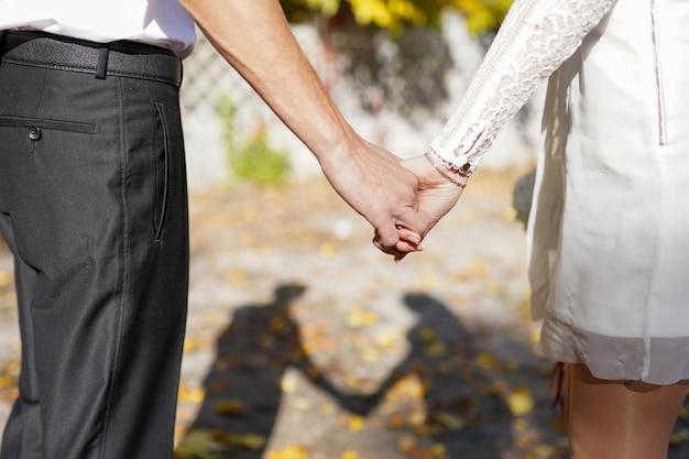 Schaduw van bruid en bruidegom hand in hand buitenshuis, gelukkig moment