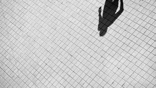 Schaduw van de mens op een bakstenen vloer
