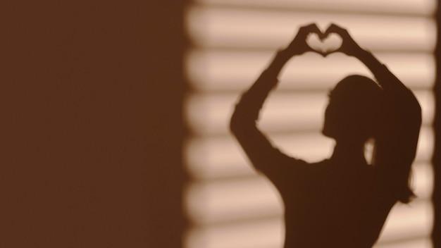Schaduw van de vrouw die een hart maakt