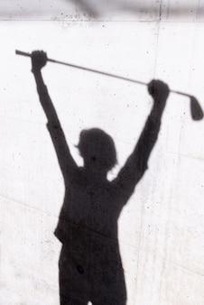 Schaduw van een golfer op de muur onder de lichten