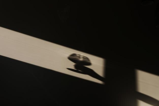 Schaduw van een hand met een wijnglas aan de muur met clair-obscur uit het raam