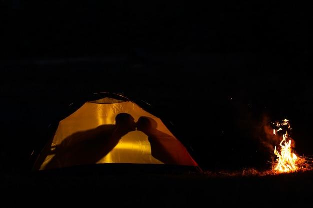 Schaduw van een paar verliefd kussen in een toeristische tent in de natuur. kamperen in de wildernis