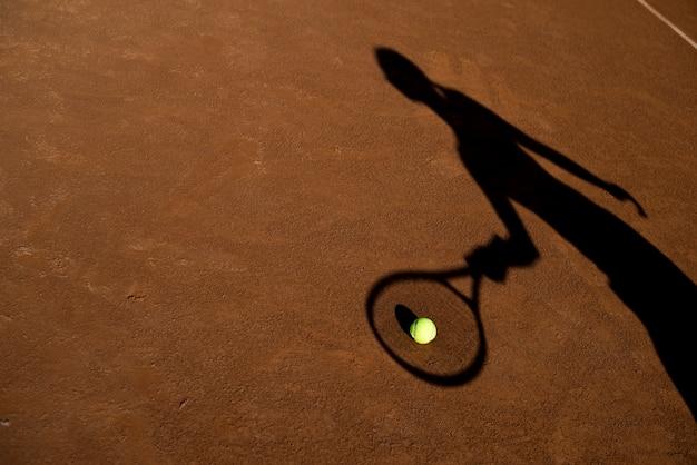 Schaduw van een tennisspeler met een bal