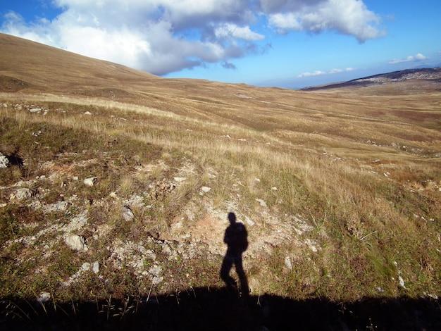 Schaduw van een vrouw met een rugzak op de achtergrond van een berglandschap in de kaukasische bergen