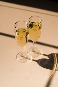 Schaduw van gevulde champagnefluit op witte achtergrond
