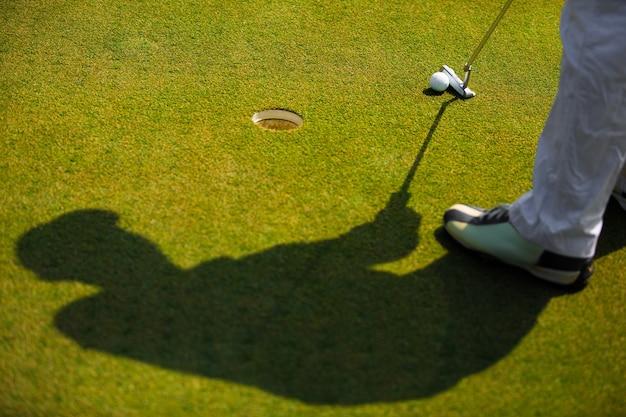 Schaduw van golfer dat gaat een golfbal slaan