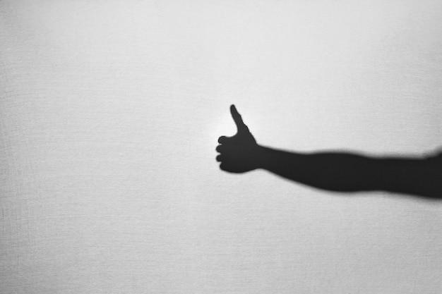 Schaduw van hand die duim toont