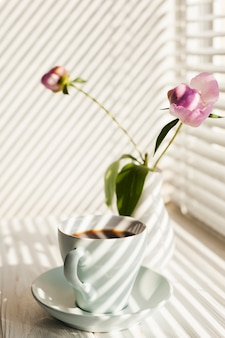 Schaduw van vensterzonneblinden op koffiekop en bloemvaas