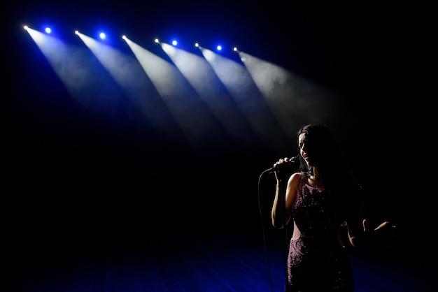 Schaduw van zanger in licht op het podium
