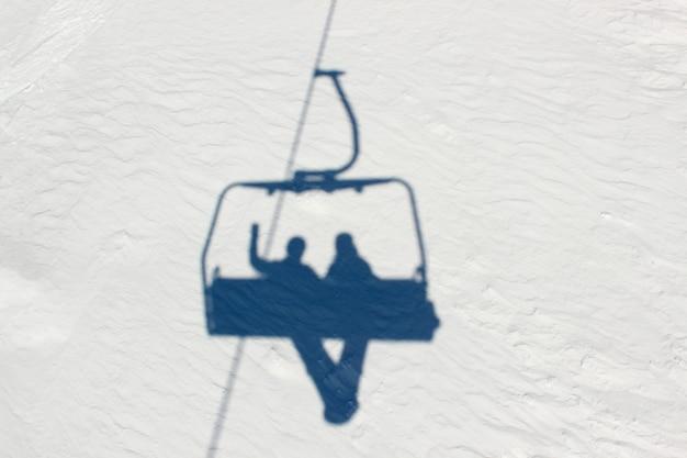 Schaduwen in de sneeuw van twee snowboarders die met een skilift de berg op gaan