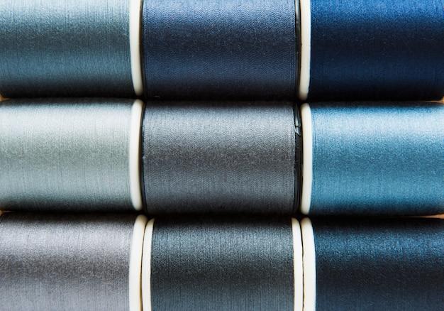 Schaduwen van grijze en blauwe naaiende draden achtergrondclose-up