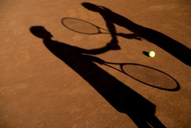 Schaduwen van twee tennisspelers
