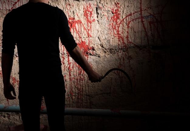 Schaduwrijke mannelijke figuur met mes in de buurt van met bloed bevlekte muur voor concept over moord en enge halloween-vakantie