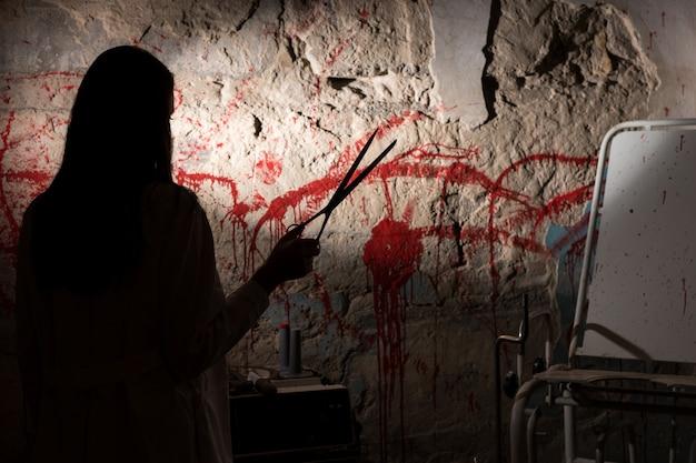 Schaduwrijke vrouwelijke figuur met een schaar in de buurt van een met bloed bevlekte muur voor concept over moord en enge halloween-vakantie