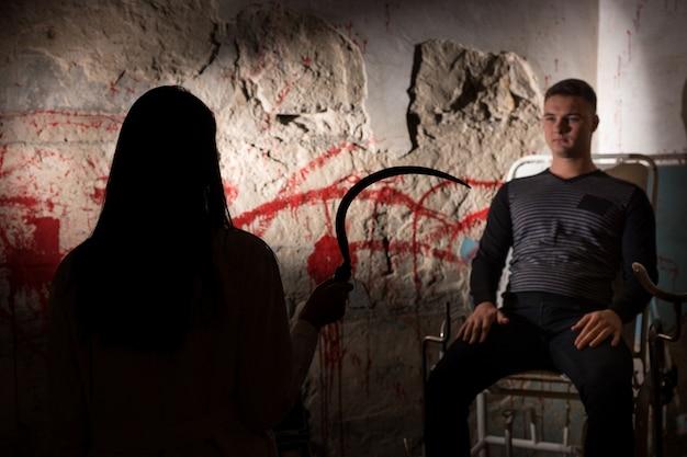 Schaduwrijke vrouwelijke figuur met grote ijzeren sikkel voor patiënt in de buurt van met bloed bevlekte muur voor concept over moord en enge halloween-vakantie