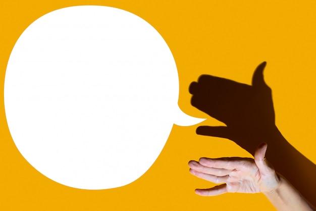 Schaduwtheater. hand toont hond met open een mond. ze heeft het op een gele achtergrond