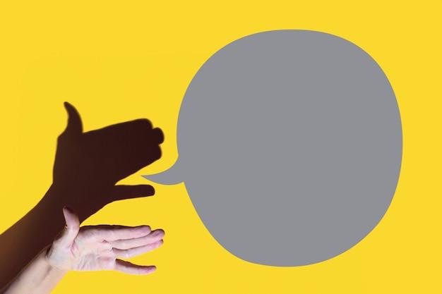 Schaduwtheater. hand toont hond met open mond. ze praat tegen een gele achtergrond.