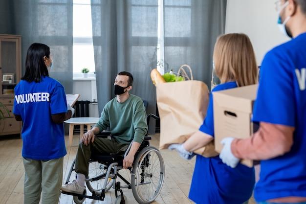 Schakel man in een rolstoel uit die met een groep jonge vrijwilligers praat