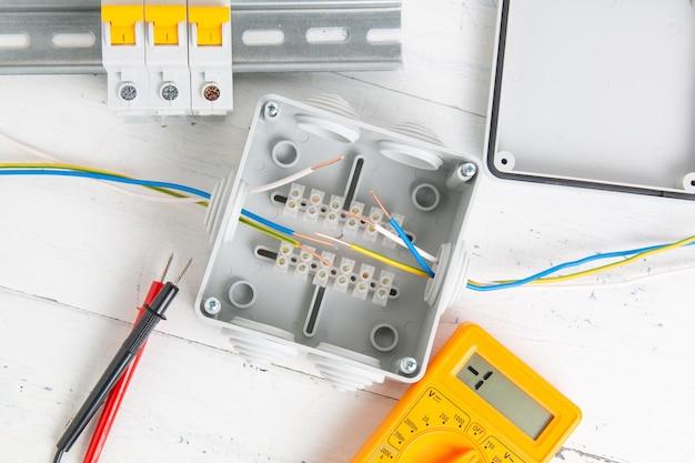 Schakelaar, stroomonderbrekers, snijbox en digitale multimeter. installatie van voedingssystemen