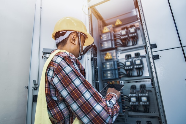 Schakelkast, control room engineer. power plant bedieningspaneel. ingenieur staande voor het bedieningspaneel in de controlekamer.