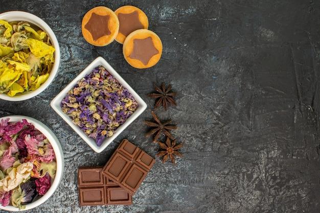 Schalen met droge bloemen en koekjes en chocoladerepen aan de linkerkant van grijs
