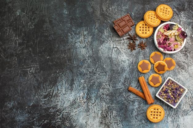 Schalen met droge bloemen met koekjes en chocoladerepen en kaneel aan de rechterkant van grijze grond