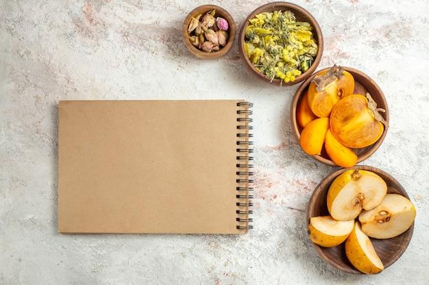 Schalen met peer en palm en droge gele bloem en lavendel en notitieboekje op marmer