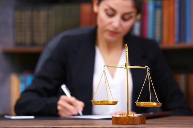 Schalen van justitie op houten tafel en vrouwelijke advocaat op achtergrond