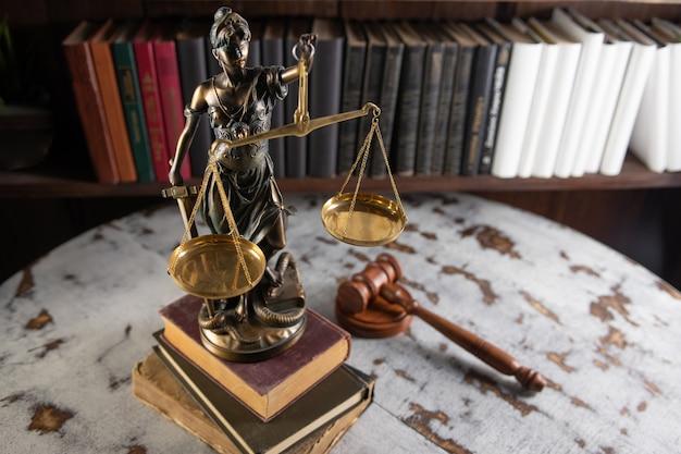 Schalen van justitie, vrouwe justitia, wet bibliotheek concept, wetboeken op de achtergrond.