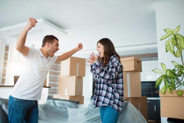 Schandaal tijdens de verhuizing naar een nieuw huis. jong koppel ruzie in een nieuw appartement in de buurt van kartonnen dozen en.