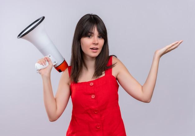 Schandalig jong kaukasisch meisje met luide spreker en opgeheven hand kijken naar camera op geïsoleerde witte achtergrond