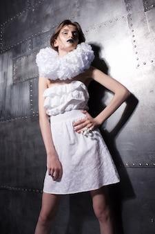 Schandalig kaukasisch meisje poseren in de modieuze witte jurk met kraag op de metalen wand.