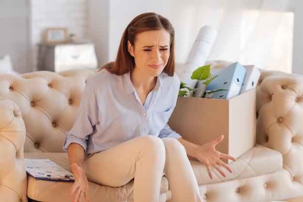 Schandelijk. emotionele wanhopige boze vrouw die zich vreselijk voelt terwijl ze thuis zit en niet gelooft in het einde van haar schitterende carrière