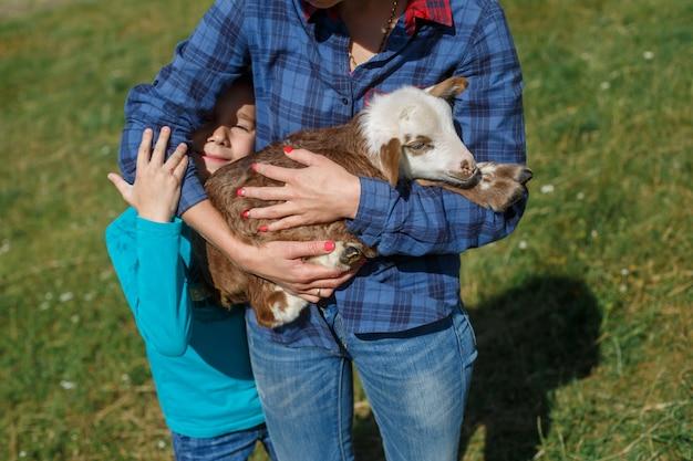 Schapen fokken boerderij buitenshuis. lachende moeder en zoon spelen op de schapenboerderij in de zomer in een zonnige dag. gelukkig weekend op de natuur in het voorjaar.
