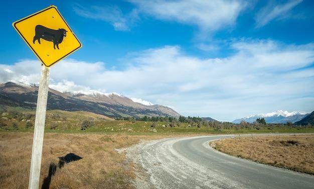 Schapenverkeersbord aan de kant van bochtige weg met bergachtergrond en blauwe hemel glenorchynew zealand