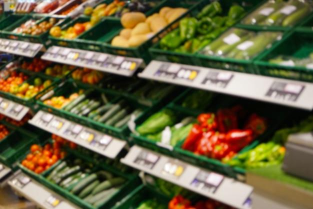 Schappen met groenten in de supermarkt, wazig