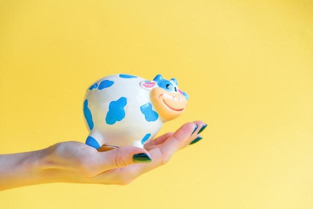 Schatbank in een menselijke hand op een gele achtergrond. de hand van een vrouw houdt een spaarvarken vol geld.