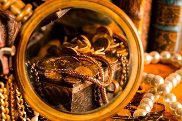 Schatkisten met goud in een vergrootglas. parels en gouden kettingen. vintage-stijl.